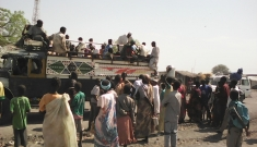 People  load into trucks to go to Sudan